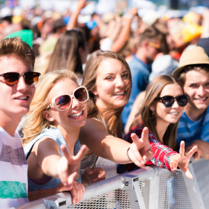 Teenagers at summer music festival under the stage in a crowd enjoying themselves, showing peace sign
